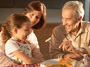 Grandparents feeding granddaughter