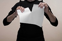 Woman tearing piece of paper close_up, midsection