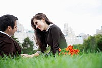 Couple sitting on grass and holding hands low angle view