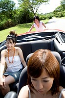 Young man pushing the car, women sitting in the car, Saipan, USA