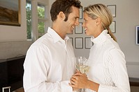 Mid adult couple holding hands and drinking champagne (thumbnail)