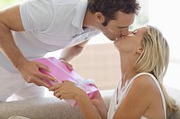 Man giving present to woman and kissing on lips
