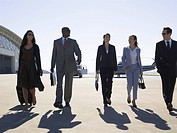 Five businesspeople walking at airport