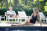 Woman lying by pool, man reading on lounge chair