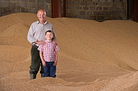 Portrait of farmer and grandson standing in wheat grain heap