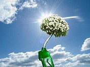 Green gas pump with blooming plant at end of nozzle