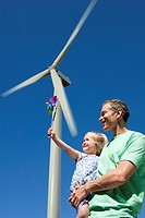 Father holding daughter with pinwheel under wind turbine