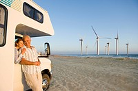 Couple hugging by motor home with wind turbines in distance