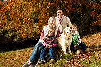 Family and dog sitting on tree stump in woods (thumbnail)