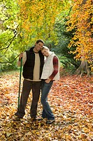 Portrait of couple with rake standing in autumn leaves