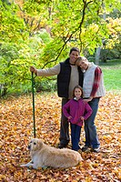 Portrait of family and dog with rake standing in autumn leaves