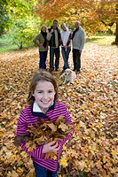 Portrait of girl holding autumn leaves with family in background