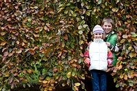 Portrait of boy and girl standing against tree