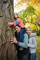 Portrait of family hugging tree trunk