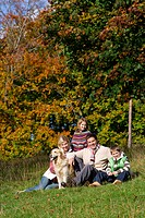 Portrait of family and dog sitting in grass