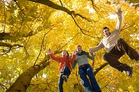 Family jumping under trees with autumn leaves