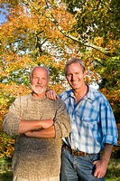 Portrait of father and son with autumn tree in background