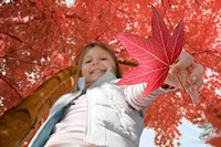 Portrait of girl holding autumn leaf