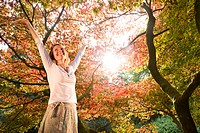 Woman standing below autumn trees with arms raised