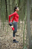 Young woman stretching hamstrings in forest