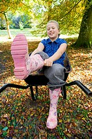 Girl sitting in wheelbarrow and putting on rubber boots