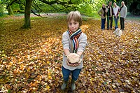 Boy holding mushroom with family in background