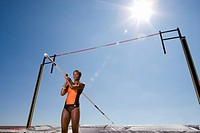 Young female pole vault athlete with pole by bar, low angle view sun flare