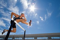 Male athlete jumping over hurdle, low angle view lens flare