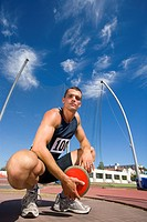 Male athlete crouching with discus, portrait, low angle view