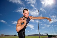 Male athlete with shot put ball, low angle view lens flare