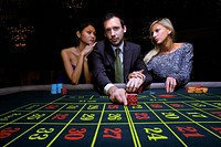Man flanked by women, gambling at roulette table, portrait, low angle view