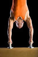 Male gymnast performing handstand on pommel horse, close_up