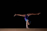 Female gymnast performing handstand on balance beam, side view