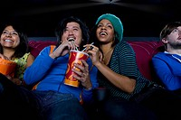 Couple sharing drink in cinema, smiling, low angle view