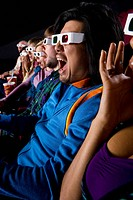 Audience in cinema wearing 3D glasses, making faces, close_up