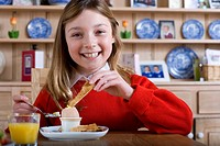Girl in school uniform having breakfast