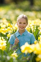 Young girl sitting in field of daffodils