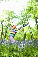 Girl running through field of bluebell flowers