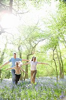 Family running through field of bluebell flowers