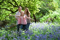 Family walking in field of bluebell flowers