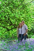 Couple standing in field of bluebell flowers