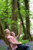 Mother and daughter relaxing on tree trunk in forest