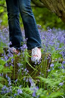 Girl balancing on log among bluebell flowers