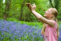 Girl holding fiddlehead fern in field of bluebell flowers