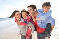 Parents piggybacking children on beach (thumbnail)