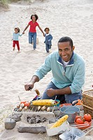 Portrait of father preparing barbecue on beach, family running in background
