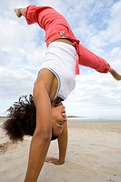 Young woman doing cartwheel on beach