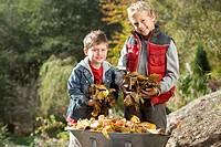 Portrait of two boys holding leaves near wheelbarrow