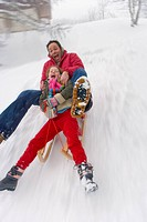 Father and daughter sledding down snow slope