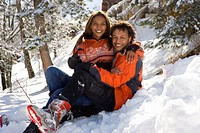 Portrait of mixed race couple sitting in snow (thumbnail)